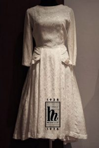 A monotone photo in cream, grey and brown. A wedding dress hangs on a mannequin. The dress is simple, with 3 /4 length sleeves and a fitted bodice with a full skirt. The textile is a textured silk brocade,