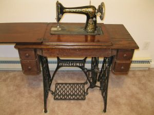 A color photo of a wooden treadle sewing machine with iron work foot plate and black and gold laminate sewing machine inserted above.