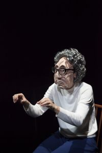 An actor wears an old lady mask on stage. She is reaching as if to pick up an invisible something in front of her.