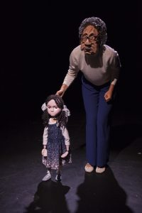 An actor is on stage wearing an old lady mask touching a small child puppet as if to encourage her to walk.