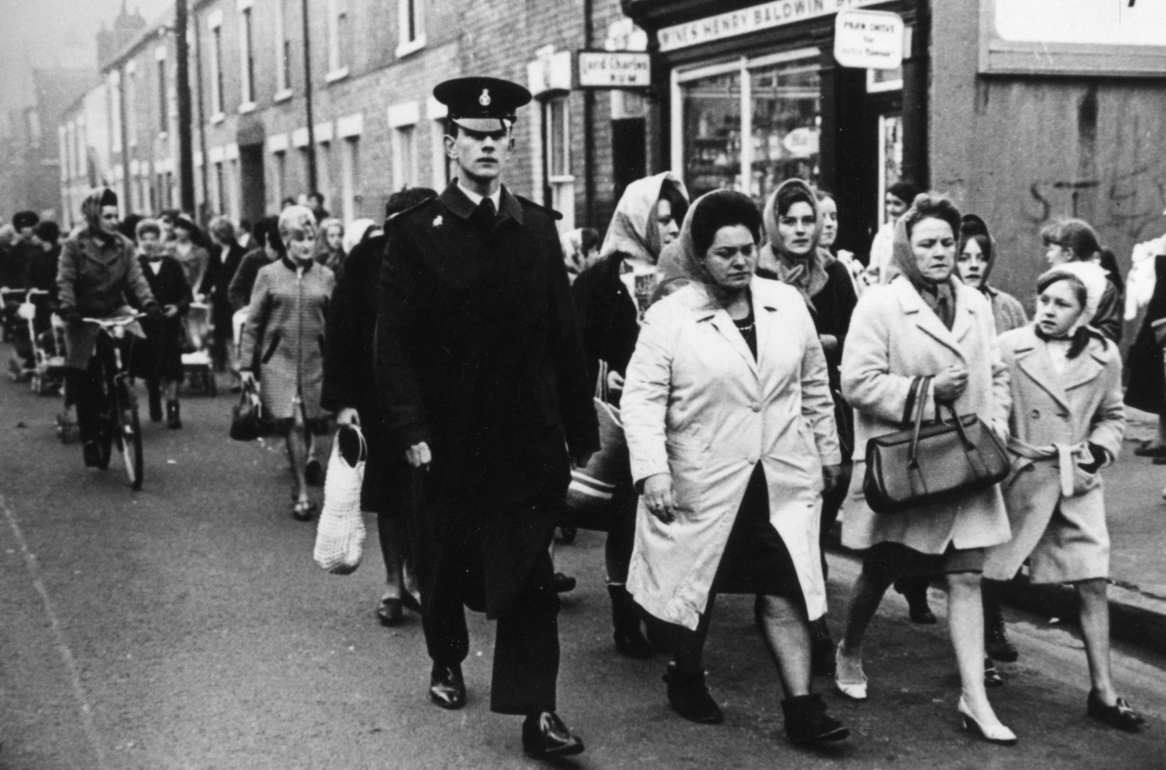 A black and white photo taken in 1968. A group of women walk purposefully along a street in Hull. They are all wearing coats and head scarves. At the front is Lillian Bilocca, the person leading the protest. Next to her is a policeman.
