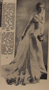 A newspaper clipping showing a wedding dress from April 1951. The gown has highwayman collar, long sleeves and a tight skirt. The train is lengthy and shown extending far from the bride's head along her body.