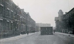 A black and white photo looking down Albion Street, Hull Royal Infirmary. In the middle of the street is a square brick building which is an air raid shelter.