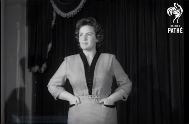 A clip from a 1950s British Pathe newsreel. A model stands on a catwalk wearing a light colored dress with 3 /4 length sleeves and a V bodice trimmed in black. The skirt is below knee length and straight, with pockets also lined in black.