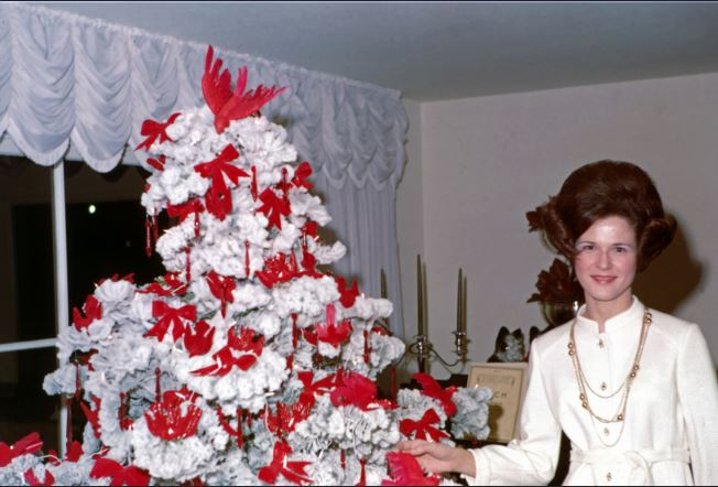 A woman wearing a 1960s kaftan next to a white faux christmas tree