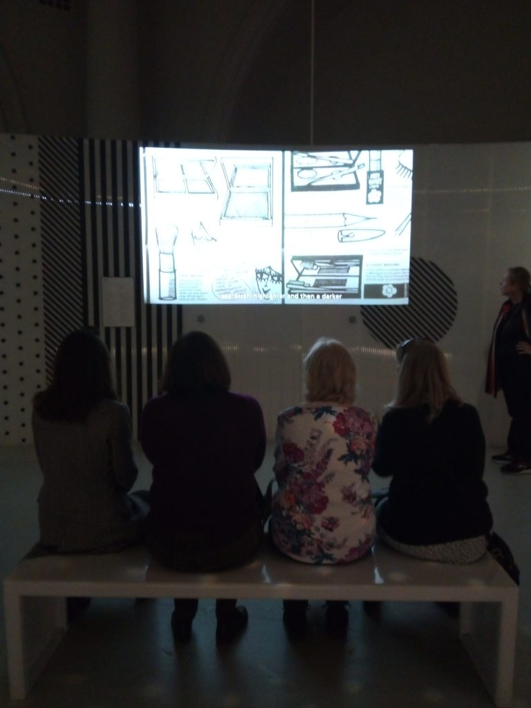 The audience watching an exhibit about make up Mary Quant